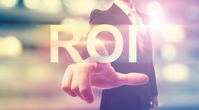 Geschäftsmann, der auf ROI (Anlagenrendite, zeigt) Stockfotos