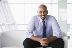 Geschäftsmann, der auf Sofa in der Vorhalle sitzt Lizenzfreie Stockfotografie