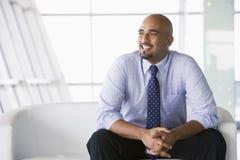 Geschäftsmann, der auf Sofa in der Vorhalle sitzt Stockfotos