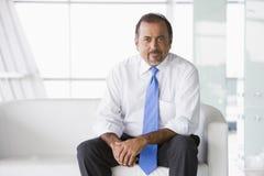 Geschäftsmann, der auf Sofa in der Vorhalle sitzt Lizenzfreie Stockbilder
