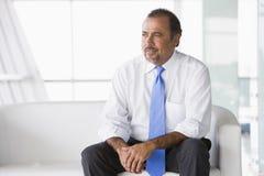 Geschäftsmann, der auf Sofa in der Vorhalle sitzt Stockbild