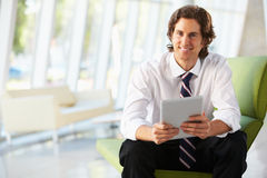 Geschäftsmann, der auf Sofa im Büro unter Verwendung Digital-Tablette sitzt Lizenzfreie Stockfotografie
