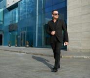 Geschäftsmann, der auf Straße nahe dem Büro geht Lizenzfreies Stockfoto