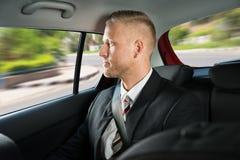 Geschäftsmann, der in Auto reist Stockbild