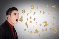 Geschäftsmann, der über Zahl von seinem Mund spricht Lizenzfreies Stockbild