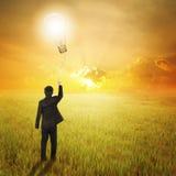 Geschäftsmann, der Birnenballon auf den Gebieten und Sonnenuntergang hält Stockfoto