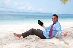 Geschäftsmann, der an dem Strand sitzt und arbeitet Lizenzfreie Stockfotografie