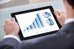 Geschäftsmann, der Diagramm auf digitaler Tablette analysiert Stockfoto
