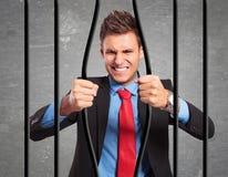 Geschäftsmann, der die Stangen seines Gefängnisses verbiegt Lizenzfreie Stockbilder
