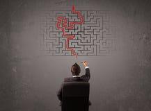 Geschäftsmann, der ein Labyrinth und den Ausweg betrachtet Stockfotografie