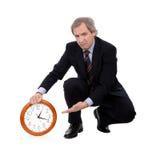 Geschäftsmann, der eine Borduhr betroffen mit Zeit anhält Stockbilder