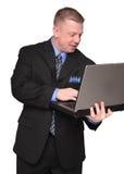 Geschäftsmann, der eine Laptop-Computer anhält Lizenzfreie Stockbilder