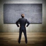 Geschäftsmann, der eine leere Wand betrachtet Stockfotografie