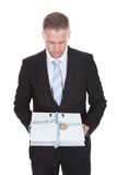 Geschäftsmann, der eine streng geheim Datei hält Stockbild