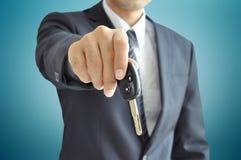Geschäftsmann, der einen Autoschlüssel - Autoverkauf u. Mietkonzept gibt Stockfotos