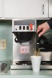 Geschäftsmann, der einen Kaffee gießt Lizenzfreies Stockfoto