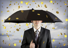 Geschäftsmann, der einen Regenschirm, Geldfallen anhält Lizenzfreie Stockfotografie