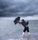 Geschäftsmann, der einen Regenschirm hält, um Regensturm zu widerstehen Stockfoto