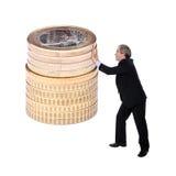 Geschäftsmann, der einen Stapel der Euromünzen drückt Stockbild
