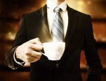 Geschäftsmann, der einen Tasse Kaffee hält Stockfoto