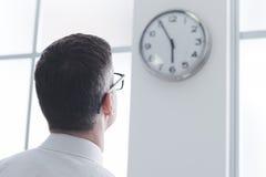 Geschäftsmann, der entlang der Uhr anstarrt Lizenzfreies Stockbild