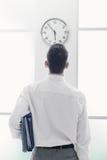 Geschäftsmann, der entlang der Uhr anstarrt Lizenzfreies Stockfoto