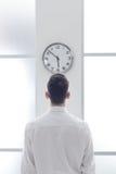 Geschäftsmann, der entlang der Uhr anstarrt Stockbild