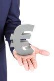 Geschäftsmann, der Eurowährungszeichen hält Stockfoto