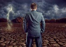 Geschäftsmann, der gegen bewölkten Himmel bleibt Lizenzfreie Stockbilder