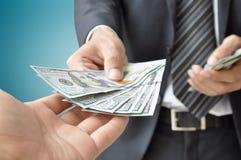 Geschäftsmann, der geld- Dollar Vereinigter Staaten gibt (U Lizenzfreies Stockbild