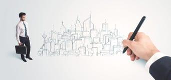 Geschäftsmann, der gezeichnete Stadt zur Hand auf Wand schaut Lizenzfreie Stockfotografie