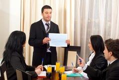 Geschäftsmann, der Grafik bei der Sitzung zeigt Stockbild