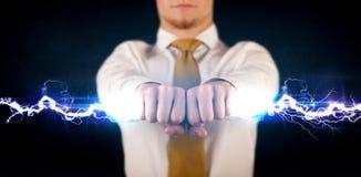Geschäftsmann, der hellen Bolzen des Stroms in seinen Händen hält Lizenzfreie Stockfotos
