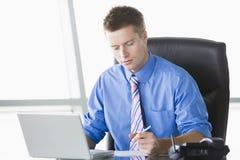 Geschäftsmann, der im Büro mit Laptopschreiben sitzt Stockfotografie
