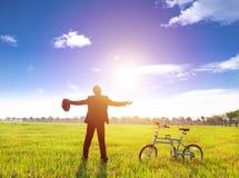 Geschäftsmann, der im grünen Land und in der Sonne mit Fahrrad sich entspannt Lizenzfreie Stockfotografie