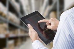 Geschäftsmann, der Inventar Raum im auf Lager einer Produktionsgesellschaft auf Tablette überprüft Stockfoto