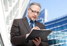 Geschäftsmann, der Kenntnisse über seine Tagesordnung nimmt Stockbild