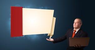 Geschäftsmann in der Klage, die einen Laptop hält Lizenzfreies Stockbild