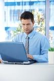 Geschäftsmann, der an Laptop arbeitet Stockfotografie