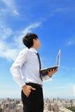 Geschäftsmann, der Laptop und Blick zum blauen Himmel verwendet Stockfoto