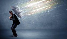 Geschäftsmann, der Lichtstrahlen mit Regenschirmkonzept verteidigt Stockfoto