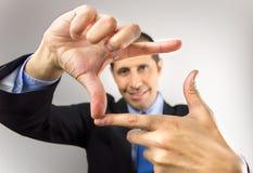 Geschäftsmann, der mit den Händen misst Stockfotografie