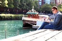 Geschäftsmann, der mit einem Laptop, draußen sitzend, nahe mit Fluss arbeitet Stockfotografie