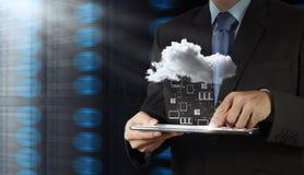 Geschäftsmann, der mit einer Wolken-Datenverarbeitung arbeitet Lizenzfreie Stockfotografie