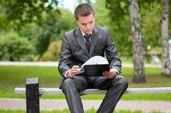 Geschäftsmann, der mit Papieren am Park arbeitet. Kursteilnehmer Lizenzfreie Stockbilder