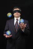 Geschäftsmann, der mit Planetenerde jongliert Lizenzfreie Stockfotos