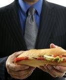 Geschäftsmann, der Schnellimbiß des Trödels isst Lizenzfreies Stockbild