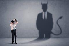 Geschäftsmann, der sein eigenes Teufeldämon-Schattenkonzept betrachtet Stockfotografie