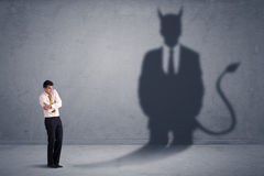 Geschäftsmann, der sein eigenes Teufeldämon-Schattenkonzept betrachtet Lizenzfreies Stockbild