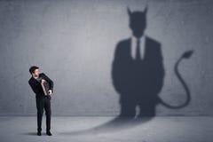 Geschäftsmann, der sein eigenes Teufeldämon-Schattenkonzept betrachtet Lizenzfreie Stockfotografie